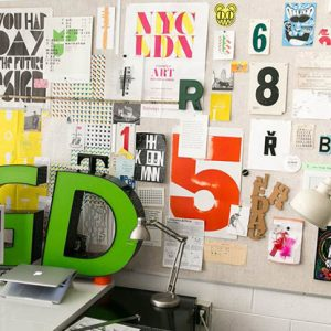 cluttered desk up against a wall covered in graphics and typography
