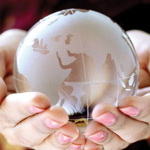 someone holding a glass globe of the world