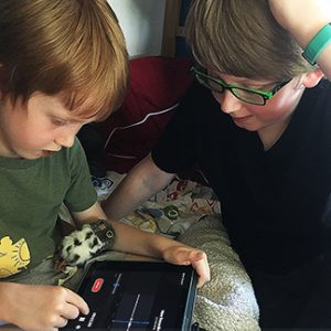 two children looking at an ipad and making voice memos